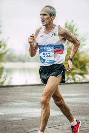 Omsk, Russia -  September 20, 2015: old man runner running along river during Siberian international marathon