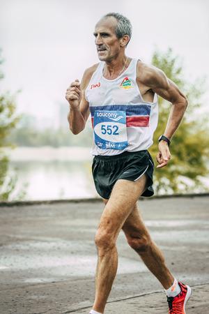 hombre viejo: Omsk, Rusia - 20 septiembre 2015: el corredor de hombre de edad a lo largo del r�o durante el marat�n internacional de Siberia