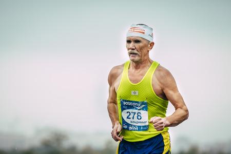 Omsk, Russia -  September 20, 2015: elderly male runner running during Siberian international marathon. background of sky 報道画像
