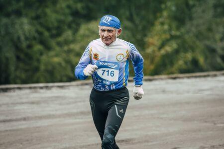 hombres corriendo: Omsk, Russia -  September 20, 2015: elderly man athlete runs along waterfront during Siberian international marathon Editorial