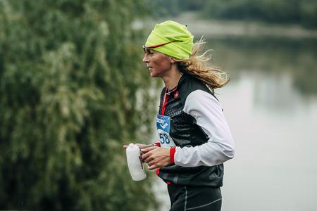 rival rivals rivalry season: Omsk, Russia -  September 20, 2015: girl athlete running along  river during Siberian international marathon
