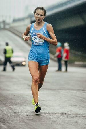 rival rivals rivalry season: Omsk, Russia -  September 20, 2015: girl participant of marathon runs through streets of city during Siberian international marathon Editorial