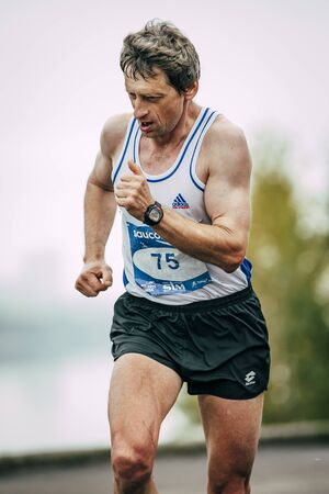 rive: Omsk, Russia -  September 20, 2015: man middle-aged runner runs along rive during Siberian international marathon