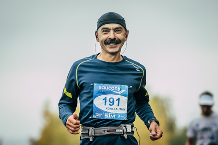 Omsk, Russia -  September 20, 2015: attractive athlete runner middle-aged distance running and smiling during Siberian international marathon Éditoriale