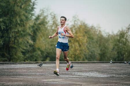 rival rivals rivalry season: Omsk, Russia -  September 20, 2015: young runner runs along river during Siberian international marathon