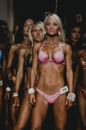 modelos posando: Chelyabinsk, Rusia - 03 de octubre 2015: Atleta rubio de fitness bikini se encuentra por delante de todos los competidores durante el Campeonato de Chelyabinsk región sobre culturismo, bodyfitness y fitness