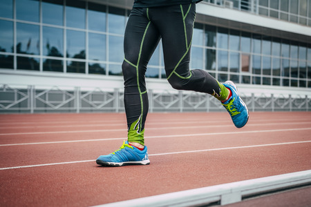 without legs: closeup legs males athlete running around track stadium.  no face, only body Stock Photo