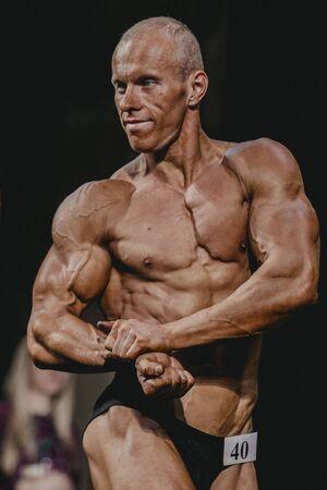 straining: Chelyabinsk, Russia - October 3, 2015: athlete bodybuilder straining biceps, side view during Championship of Chelyabinsk region on bodybuilding, bodyfitness and fitness
