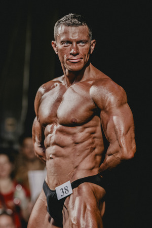 straining: Chelyabinsk, Russia - October 3, 2015: handsome male bodybuilder straining press during Championship of Chelyabinsk region on bodybuilding, bodyfitness and fitness