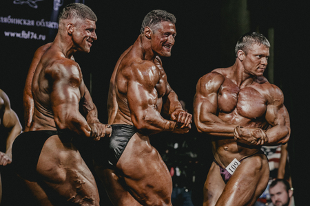 Chelyabinsk, Russia - October 3, 2015: group of men bodybuilder side view showing biceps of his arms during Championship of Chelyabinsk region on bodybuilding, bodyfitness and fitness