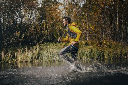 surmount: Beloretsk, Russia -  September 26, 2015: male runner crossing a mountain river, around him water splashes during marathon mountain Big Iremel