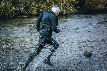 surmount: Beloretsk, Russia -  September 26, 2015: male athlete crossing the river on rocks side view during marathon mountain Big Iremel Editorial