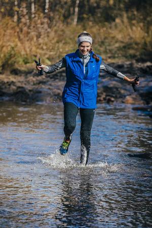 surmount: Beloretsk, Russia -  September 26, 2015: young girl athlete crossing a mountain river during marathon mountain Big Iremel Editorial