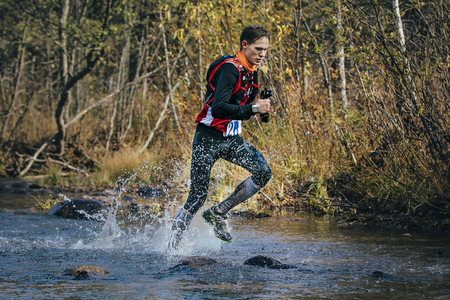 surmount: Beloretsk, Russia -  September 26, 2015: Young man runner splash water in river, during crossing a mountain river, marathon mountain Big Iremel