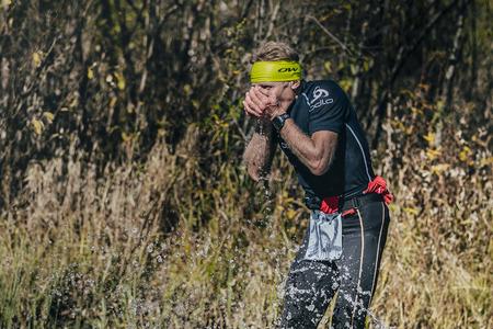 surmount: Beloretsk, Russia -  September 26, 2015: runner man drinks water from a mountain stream during marathon mountain Big Iremel