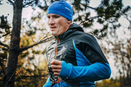 jogging track: Beloretsk, Russia -  September 26, 2015: closeup of male runner of middle-aged runs through forest during marathon mountain Big Iremel
