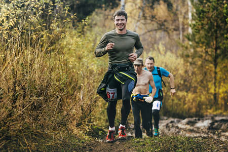trails: Beloretsk, Russia -  September 26, 2015: beautiful smiling man running in autumn forest during marathon mountain Big Iremel