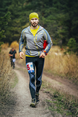 rivals rival rivalry season: Beloretsk, Russia -  September 26, 2015:young male runner running through forest road during marathon mountain Big Iremel Editorial