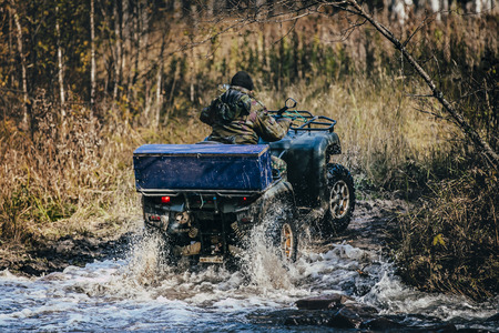 Forester ATV rides through autumn forest through a river crossing