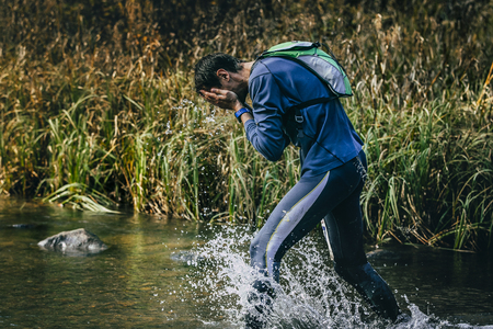 surmount: male athlete running across river. Rinses face with water