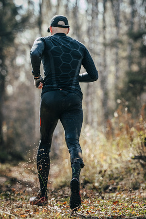 rival rivals rivalry season: male runner running in autumn forest, water stains from clothes. view from back