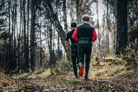 rival rivals rivalry season: two men runner running in autumn forest during mountain marathon. view from back
