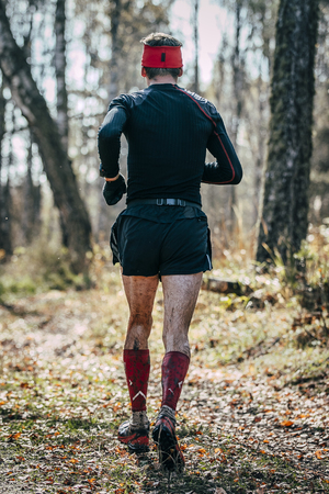 rival rivals rivalry season: male runner running in autumn forest, wet feet and mud. view from back Stock Photo