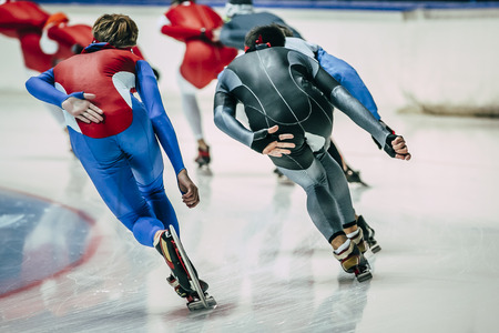 skaters: men speed skaters in training. view from back
