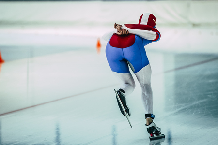 rear view girl: rear view girl speed skaters goes on ice stadium