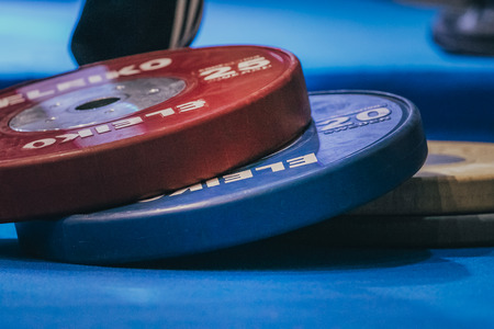powerlifting: Ekaterinburg, Russia - October 17, 2015: blue and red discs for barbell during Tournament powerlifting and bodybuilding Golden tiger Editorial
