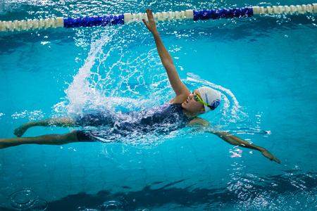 backstroke: Chelyabinsk, Russia - October 21, 2015: young beautiful girl swims backstroke during Championship of Chelyabinsk swimming