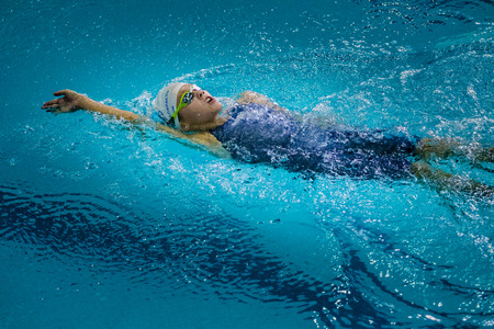 Chelyabinsk, Russia - October 21, 2015: young charming girl swims backstroke during Championship of Chelyabinsk swimming Éditoriale