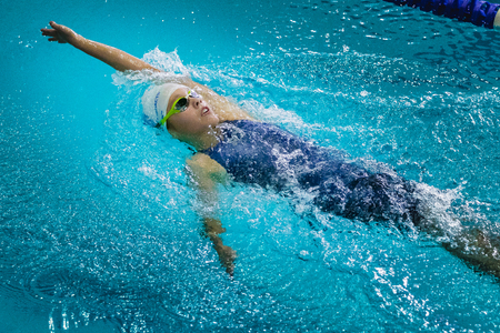 swimming race: Chelyabinsk, Russia - October 21, 2015: young beautiful girl athlete swims backstroke during Championship of Chelyabinsk swimming