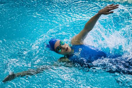 backstroke: Chelyabinsk, Russia - October 21, 2015: girl athlete swims backstroke, around her spray of water during Championship of Chelyabinsk swimming