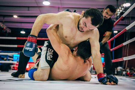 artes marciales mixtas: Volgograd, Russia - October 24, 2015: two fighters mixed martial arts fight on floor of  ring during Championship of Russia on mixed martial arts Editorial