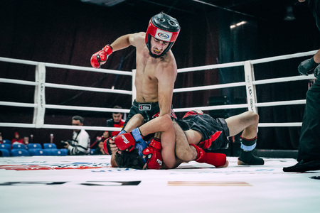 mixed martial arts: Volgograd, Russia - October 24, 2015: fighter mixed martial arts blow to head opponent lying on floor during Championship of Russia on mixed martial arts