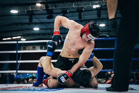 Volgograd, Russia - October 24, 2015: MMA fighter gets a direct hit a hand on head of an opponent lying on floor ring during Championship of Russia on mixed martial arts Editorial