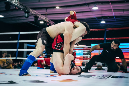 opponent: Volgograd, Russia - October 24, 2015: MMA fighter strikes hand on head of an opponent lying on floor ring during Championship of Russia on mixed martial arts