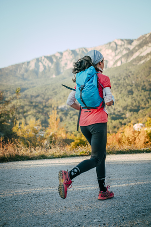 rival rivals rivalry season: young girl running mountain marathon on road. background of mountain landscape Stock Photo