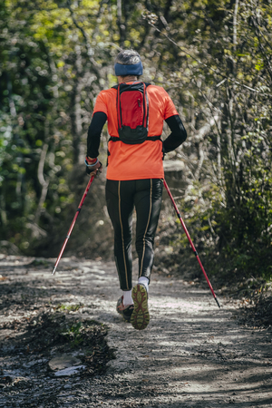 marathon: elderly athlete man running mountain marathon along a forest trail with a backpack and walking sticks