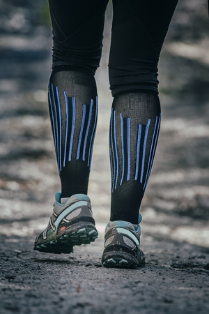 socks: closeup feet of runner in black compression socks and running shoes for mountain running