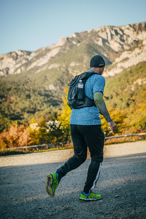 rivals rival rivalry season: Yalta, Russia - October 31, 2015: young male athlete runs in background of mountain landscape during First Yalta mountain marathon