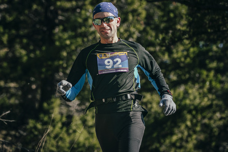 real man: Yalta, Russia - October 31, 2015: young smiling man with glasses runner is running through woods during First Yalta mountain marathon