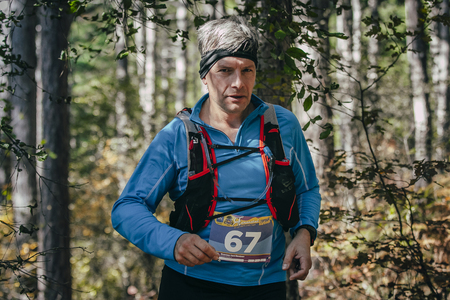 rival rivals rivalry season: Yalta, Russia - October 31, 2015: athlete middle-aged man runs through forest during First Yalta mountain marathon Editorial