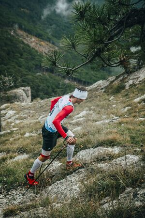 kilometre: Yalta, Russia - November 2, 2015: male athlete climbs on foot uphill during Mountain marathon Vertical kilometre AI-Petri