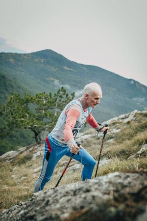 "Yalta, Russia - November 2, 2015: male athlete senior years with walking sticks going uphill during Mountain marathon ""Vertical kilometre AI-Petri"""