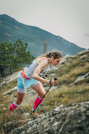 kilometre: Yalta, Russia - November 2, 2015: girl athlete with walking sticks going uphill during Mountain marathon Vertical kilometre AI-Petri