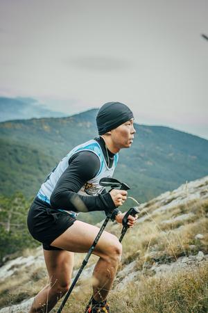 rival rivals rivalry season: Yalta, Russia - November 2, 2015: young athlete with nordic walking poles is on side of mountainduring Mountain marathon Vertical kilometre AI-Petri Editorial