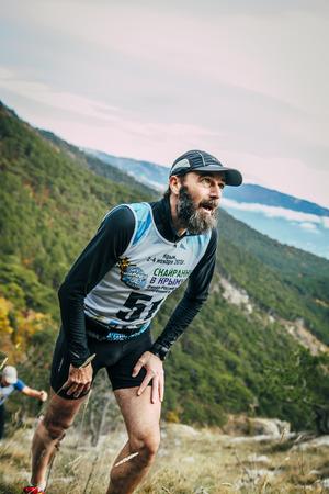 rival rivals rivalry season: Yalta, Russia - November 2, 2015: male athlete middle-aged rises to top of mountain during Mountain marathon Vertical kilometre AI-Petri