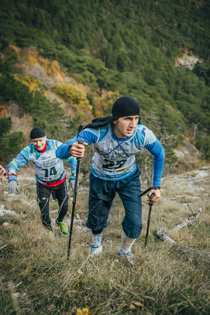 Yalta, Russia - November 2, 2015: young athlete marathon runner is ahead of his opponent on a mountain trail during Mountain marathon Vertical kilometre AI-Petri Editorial